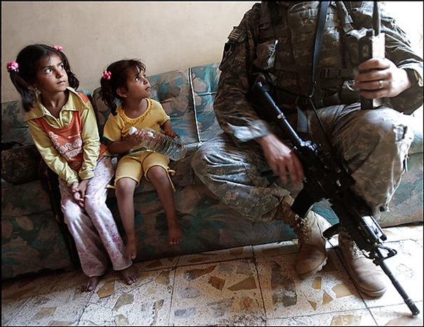 BAGHDAD, IRAQ - JUNE 21:  Two Iraqi girls watch Staff Sgt. Nick Gibson of the 2nd Battalion, 12th Infantry Regiment of the 2nd Infantry Division June 21, 2007 as the unit was canvassing the tense Dora neighborhood of Baghdad, Iraq.  U.S. soldiers patrol the area almost daily in an effort to get to know the residents and find insurgents.