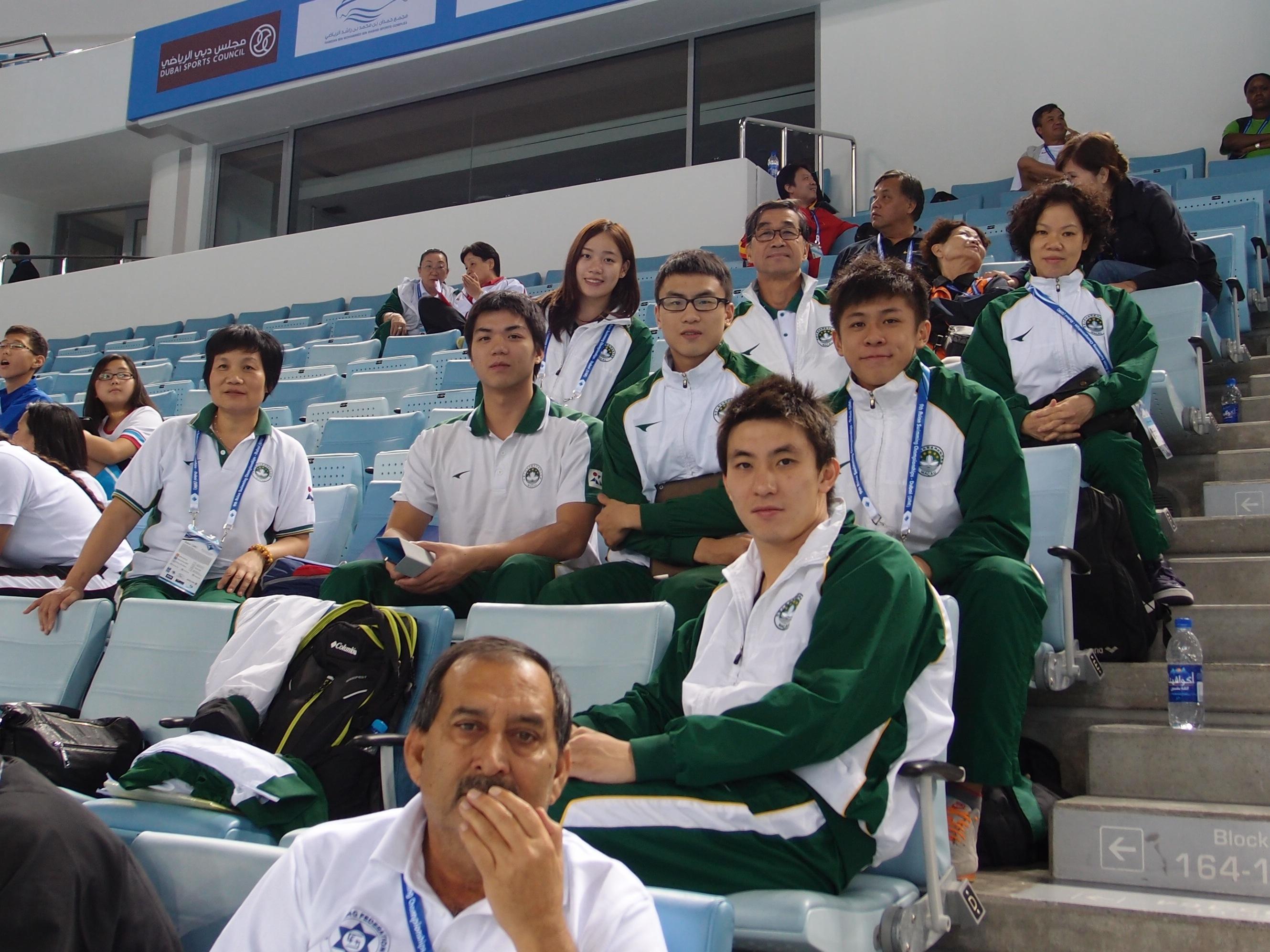 游泳代表團團長麥志權、應静莉教練、李富嬋教練及代表隊運動員在觀眾席為澳門女子接力隊打氣。