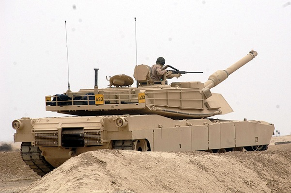 An Iraqi tank crew member loads a .50 caliber machine gun during a live fire training exercise with an M1 Abrams tank, in Baghdad, Iraq, Nov. 14. Photo by Spc. Jesse Gross