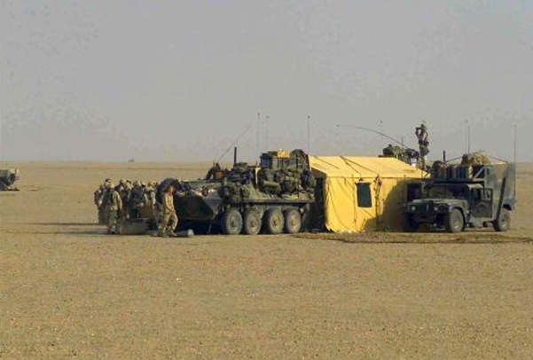 Marines assigned to 5th Marine Regiment use Command and Control Light Armored Vehicles (LAV-25) and a M1097A2 High-Mobility Multipurpose Wheeled Vehicle (HMMWV) equipped with a Common Ground Station (CGS) shelter, to set up the Combat Operations Center in Kuwait.